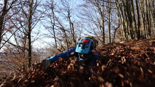 mountain biker ploughs through freshly fallen leaves - マウンテンバイク点の映像素材/bロール