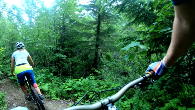mountain biker point of view following young woman down rugged west coast trail - young men stock videos & royalty-free footage