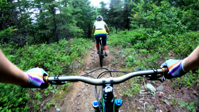 mountain biker point of view following young woman down rugged west coast trail - sports equipment stock videos & royalty-free footage