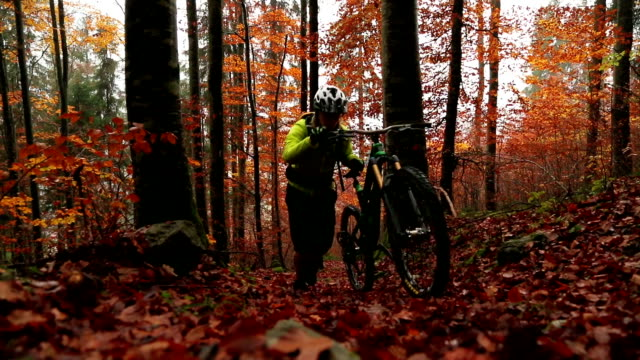 mountain biker pushes his bike up wet leafy forest path - cycling helmet stock videos & royalty-free footage