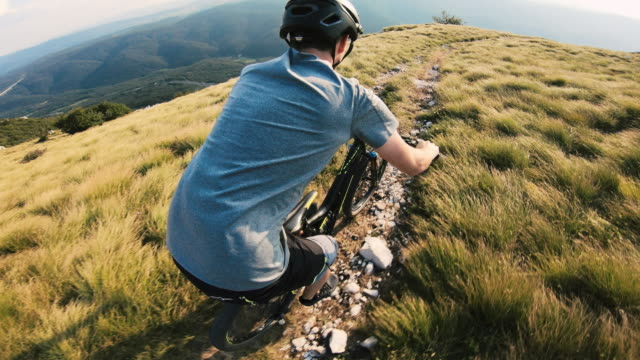 mountain biker racing down a mountain trail - mountain biking stock videos & royalty-free footage