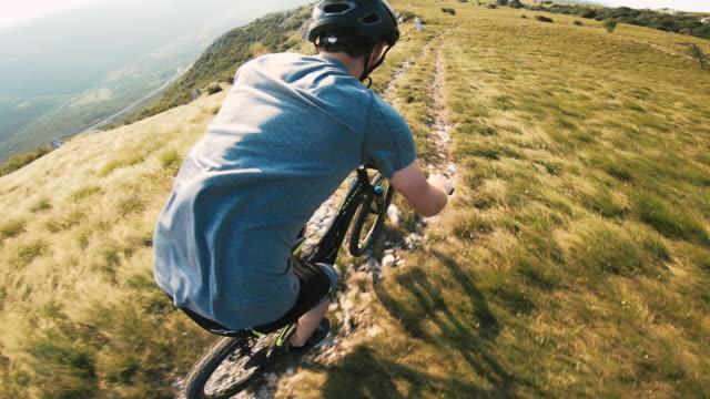 vídeos de stock e filmes b-roll de mountain biker racing down a mountain trail - cavalgada de lazer