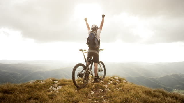 SLO MO mountain biker raising his hands at the top