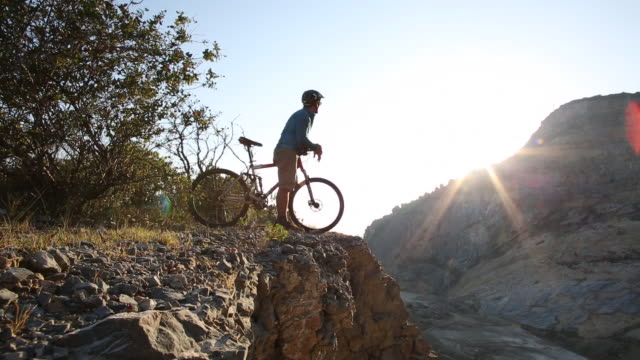 mountain biker reaches ridge crest, looks off towards sunrise - at the edge of stock videos and b-roll footage