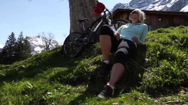 Mountain biker relaxes below Eigerwand, in green meadow