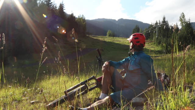 Mountain biker relaxes on meadow slope, at sunrise