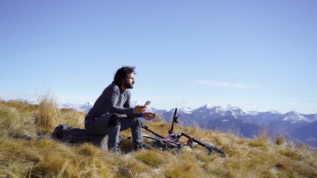 vídeos y material grabado en eventos de stock de mountain biker resting on mountain top eat energy bar while using smartphone - un solo hombre