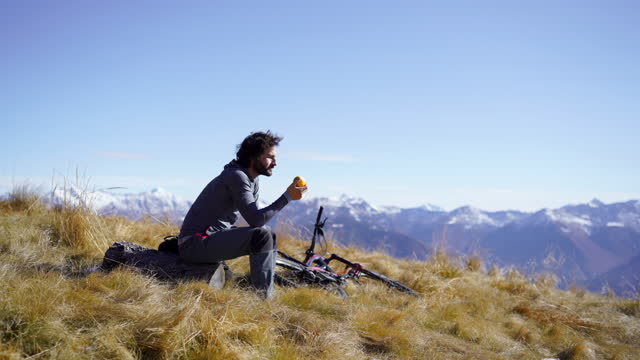 mountain biker resting on mountain top throws apple in the air then starts eating it - one mid adult man only stock videos & royalty-free footage