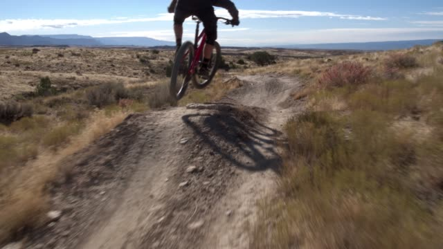 a mountain biker rides a desert trail on 18 road in fruita, colorado - andare in mountain bike video stock e b–roll