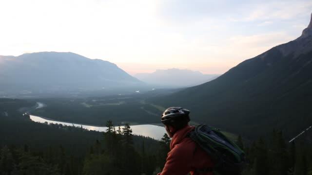 vídeos y material grabado en eventos de stock de mountain biker rides along mountain ridge crest, sunrise - sólo hombres jóvenes