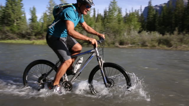 Mountain biker rides bicycle into river shallows, through forest