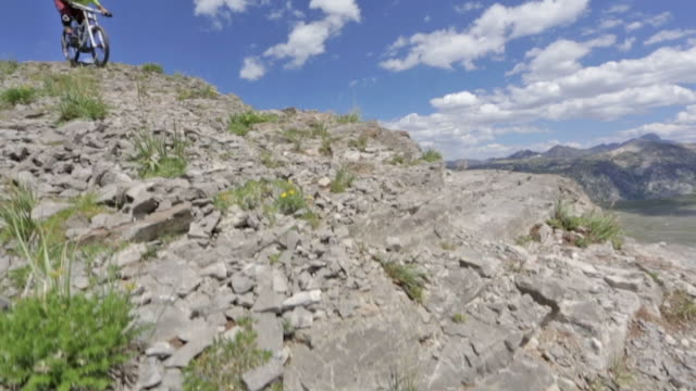 vídeos de stock e filmes b-roll de a mountain biker rides down a rocky path at grand targhee in wyoming - enfeites para a cabeça