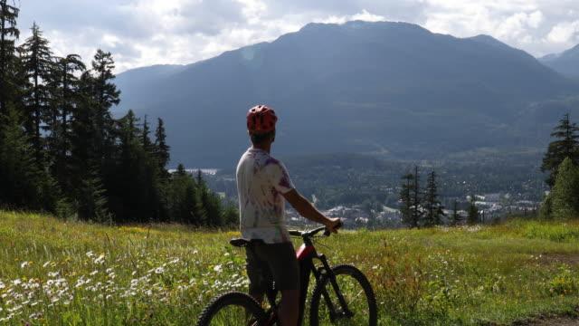 mountain biker rides e-bike through alpine meadow - lockdown viewpoint stock videos & royalty-free footage
