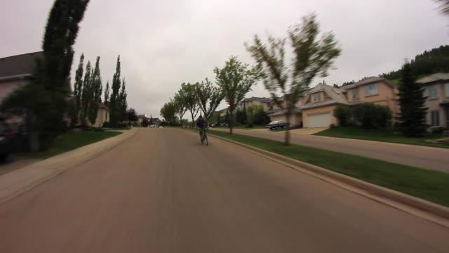 a mountain biker rides fast down a neighborhood road. - slow motion - 乗物後部から見た視点点の映像素材/bロール