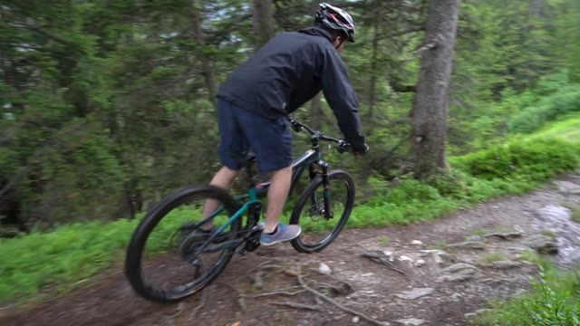 a mountain biker rides on a singletrack trail in the rain. - slow motion - leeds stock videos and b-roll footage