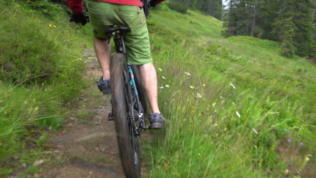 a mountain biker rides on a singletrack trail. - slow motion - mountain bike stock videos and b-roll footage