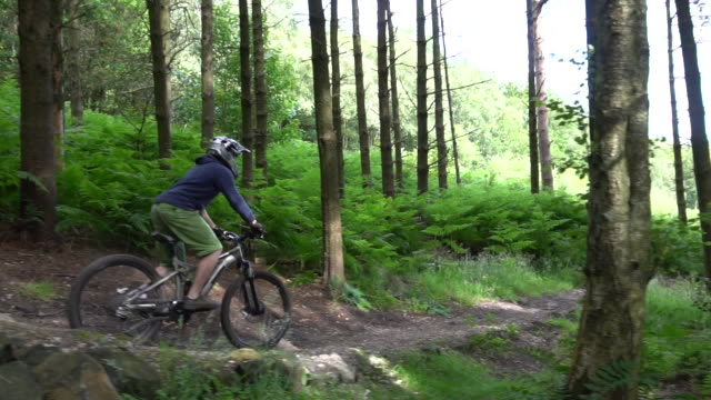 a mountain biker rides on a singletrack trail. - slow motion - goodsportvideo stock videos and b-roll footage
