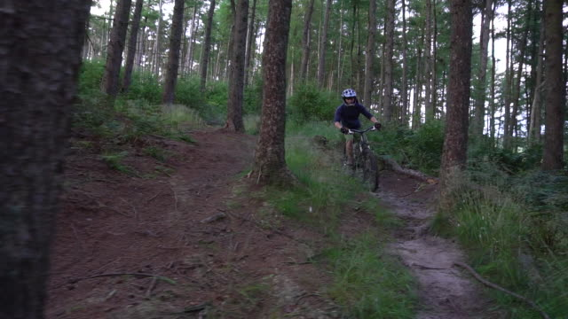 a mountain biker rides on a singletrack trail. - slow motion - nur junge männer stock-videos und b-roll-filmmaterial