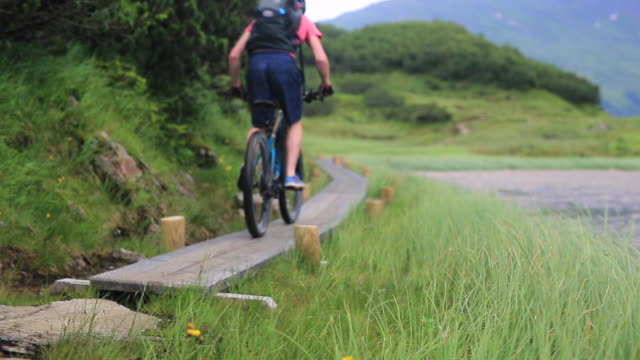 a mountain biker rides on a singletrack trail. - nur junge männer stock-videos und b-roll-filmmaterial
