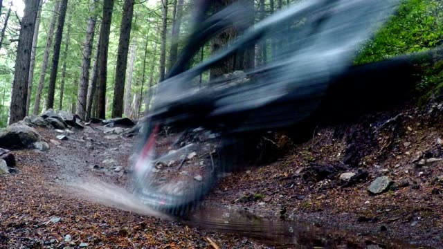 mountain biker rides through a puddle - mountain biking stock videos & royalty-free footage