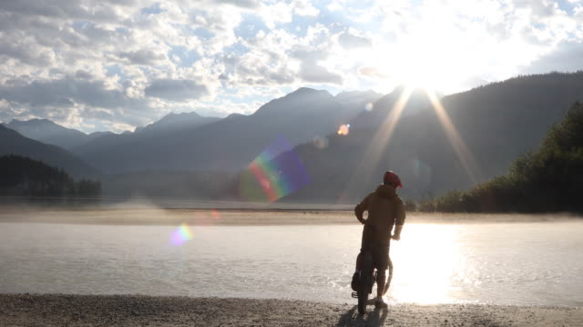 mountain biker rides to river edge, looks out over lake - at the edge of stock videos & royalty-free footage