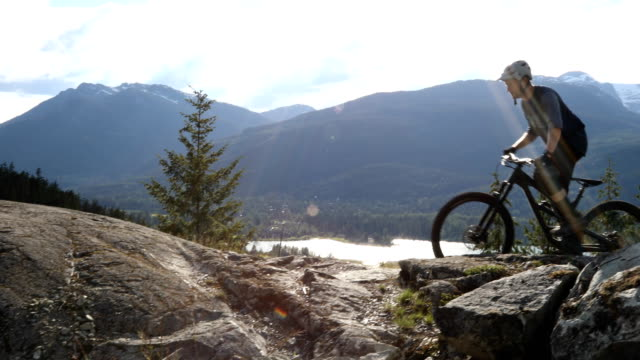 Mountain biker rides up high mountain rock slab above mountain lake view.
