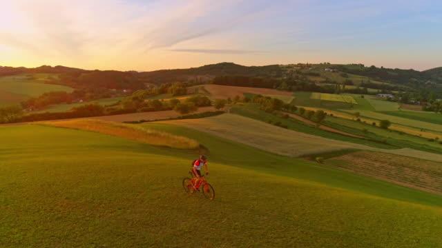 AERIAL SLO MO Mountainbiker mit dem Fahrrad auf einer Wiese