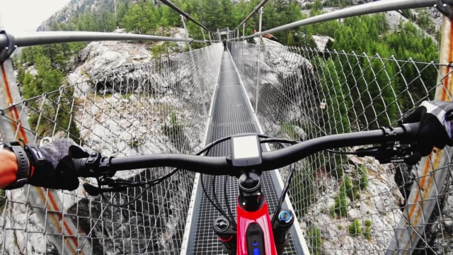 mountain biker riding across suspension bridge pov - extreme sports point of view stock videos & royalty-free footage