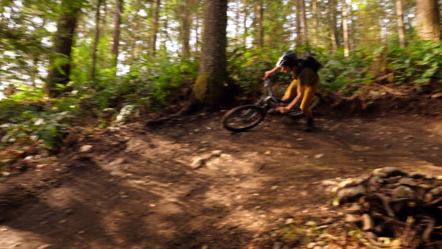 pan mountain biker riding around corner on bike trail in forest - sports helmet stock videos & royalty-free footage