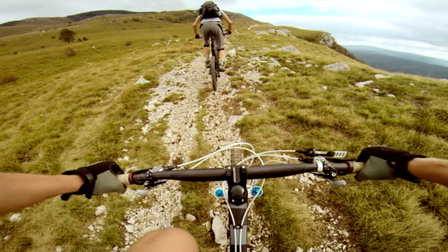 pov mountain biker riding behind his friend - home video camera stock videos and b-roll footage