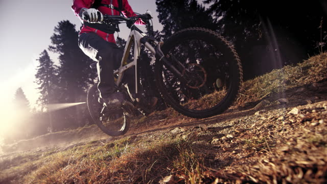 slo mo mountain biker riding down a rocky trail in sunshine - biker jacket stock videos and b-roll footage