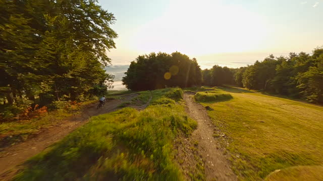 aerial mountain biker riding down the racetrack in the morning - tracking shot stock videos & royalty-free footage