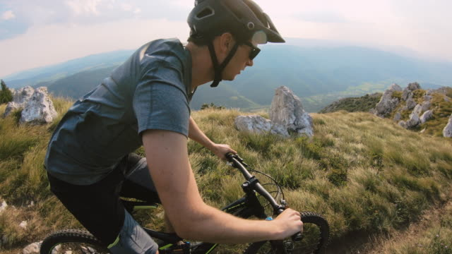 mountainbiker, die einen bergpfad bergab - mountainbiking stock-videos und b-roll-filmmaterial