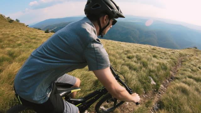 vídeos de stock e filmes b-roll de mountain biker riding downhill a mountain trail - cavalgada de lazer