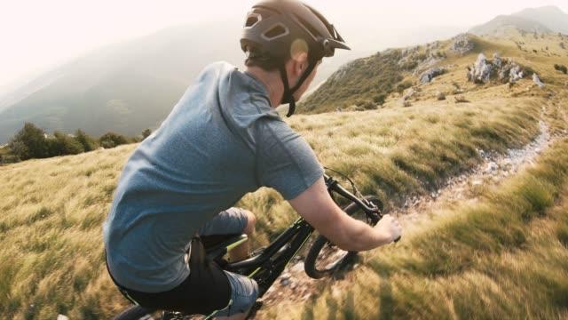vídeos de stock e filmes b-roll de mountain biker riding downhill across rocky mountain landscape on a sunny day - cavalgada de lazer