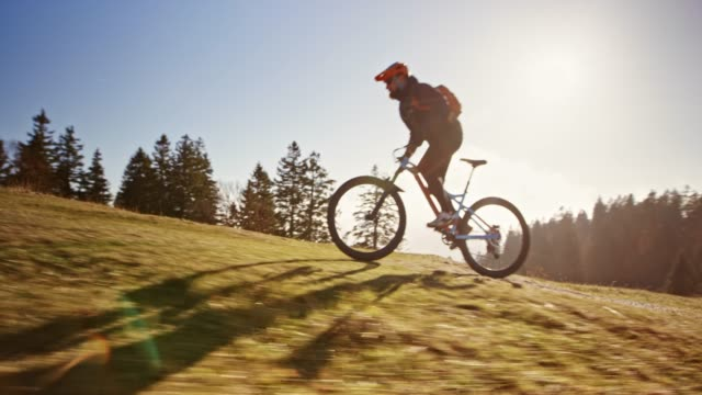 ts mountain biker riding fast up the mountain meadow in sunshine - mountain bike video stock e b–roll