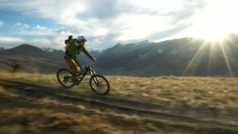 vidéos et rushes de mountain biker riding mountain ridge at sunset - faire du vélo tout terrain