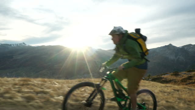 Mountain biker riding mountain ridge at sunset