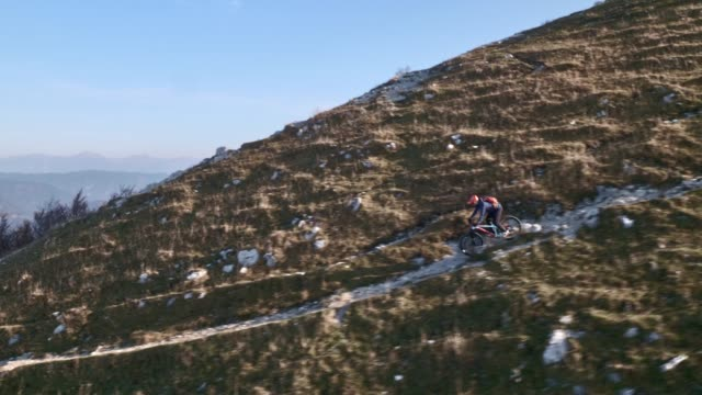 aerial mountain biker riding on a gravel path down a mountain in sunshine - jacket stock videos & royalty-free footage