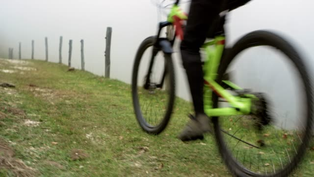mountain biker riding on a mountain path in fog - motorcycle biker stock videos & royalty-free footage