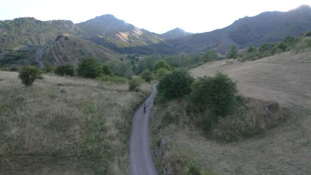 vídeos y material grabado en eventos de stock de mountain biker riding on a rural country road in summer, aerial view - campo lugar deportivo