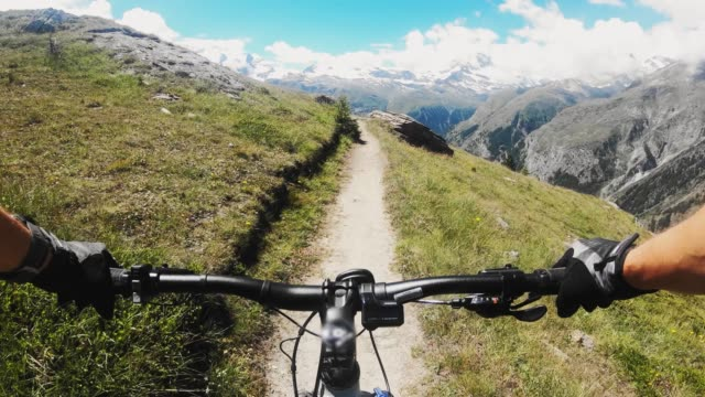 pov mountain biker riding on a trail with with views of swiss alps - extreme sports point of view stock videos & royalty-free footage