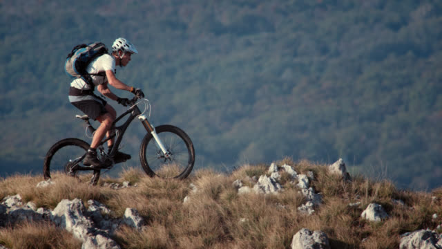 slo mo mountain biker riding on the ridge - mountain biking stock videos & royalty-free footage
