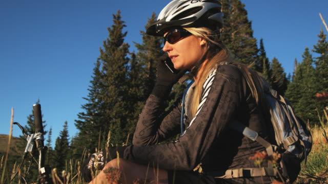 vídeos y material grabado en eventos de stock de mountain biker sitting down to make a phone call - brighton ski area