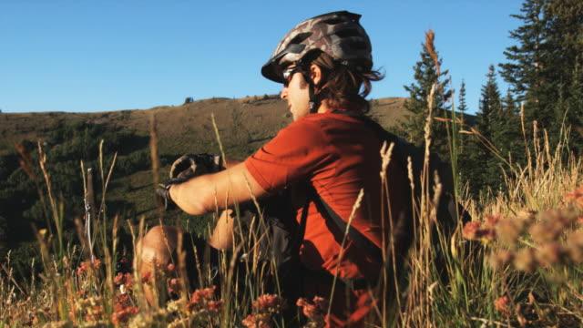vídeos y material grabado en eventos de stock de mountain biker sitting down to rest - brighton ski area