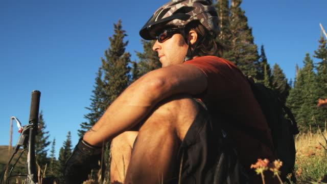 mountain biker sitting down to rest - stazione sciistica di brighton video stock e b–roll
