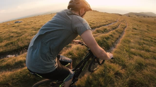 mountain biker speeding down a mountain trail at sunset - recreational horseback riding stock videos & royalty-free footage