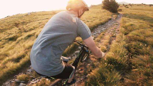 vídeos de stock e filmes b-roll de mountain biker speeding down a mountain trail at sunset - cavalgada de lazer