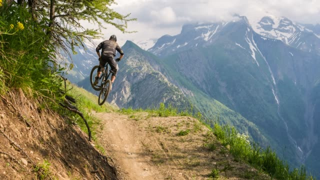 mountain biker speeding downhill, jumping on dirt trail, doing a stunt - mountain bike stock videos & royalty-free footage