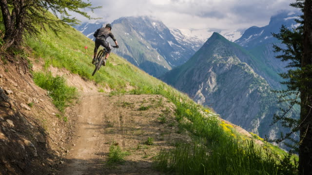 mountain biker speeding downhill, jumping on dirt trail - andare in mountain bike video stock e b–roll